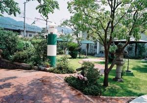 この庭のシンボルになっている灯台。グランドコンクリートのアプローチは緩やかに曲線を描きながら玄関へと続いています。